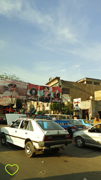 Foto de uma rua no Cairo, com automóveis bem antigos.