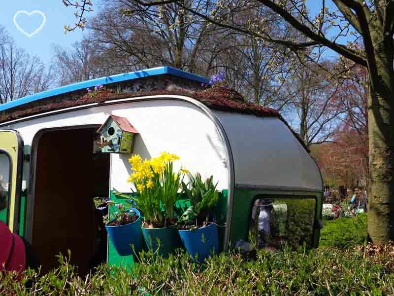 Foto de um trailer antigo decorado com flores e uma casinha de passarinho, de madeira.