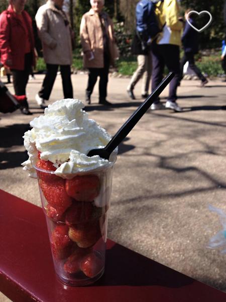 Foto de um copo com morangos e chantilly.