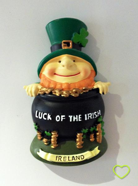 """Foto de um ímã de geladeira em forma de um leprechaun com um pote cheio de moedas de ouro, onde se vê escrito """"luck of the irish"""". O leprenchaun tem a barba ruiva alaranjada e usa uma cartola verde com um trevo."""