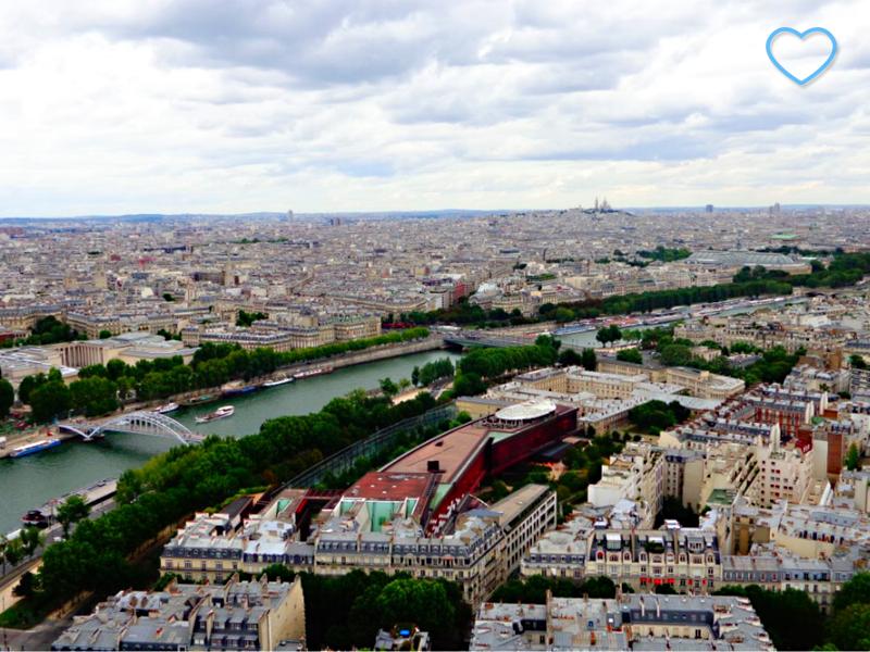 Foto do rio Sena cruzando Paris, uma cidade cheia de edifícios e algumas árvores.