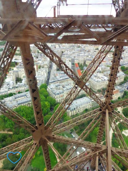 Foto tirada de dentro do elevador. Dá para ver a estrutura da torre e a cidade.