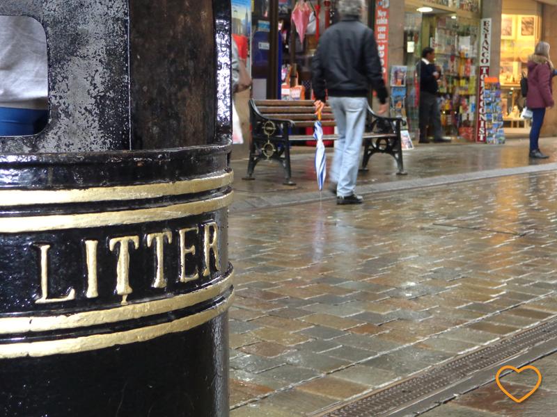 Foto com a lixeira em primeiro plano, mostrando a palavra que está nela, Litter. Em segundo plano, o calçadão com pedrestes.