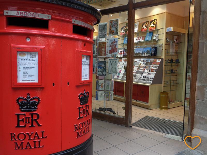 Foto com a caixa de correio em primeiro plano, com a coroa, as letras E e R e as palavras Royal Mail. Em segundo plano, a loja dos correios, com cartões postais.