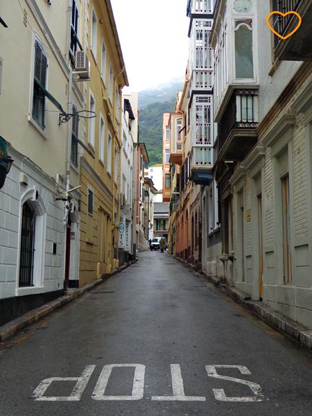 Foto de uma rua estreita. O rochedo aparece ao fundo.