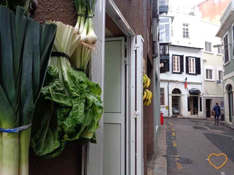 Uma loja tipo hortifruti com verduras e cachos de banana pendurados na fachada, como decoração.