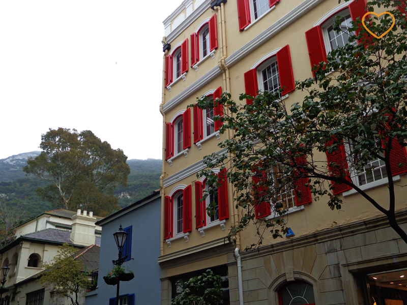 Foto de uma fachada de um edifício e umas casas e o rochedo ao longe.