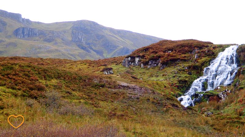 Foto de uma montanha em primeiro plano com um cachoeira e uma montanha em segundo plano.