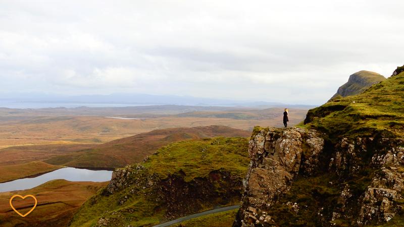 Imagem quase que panorâmica do vale e uma parte de uma montanha. Uma pessoa está de pé em um dos planos escarpados.