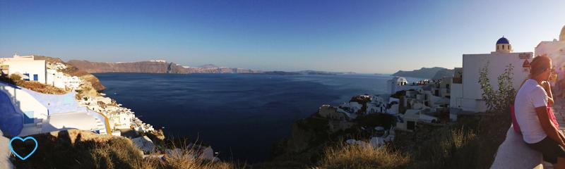 Foto panorâmica mostrando uma ponta da ilha com casinhas brancas e a outra com uma igrejinha de cúpula azul. Vê-se o mar no meio.