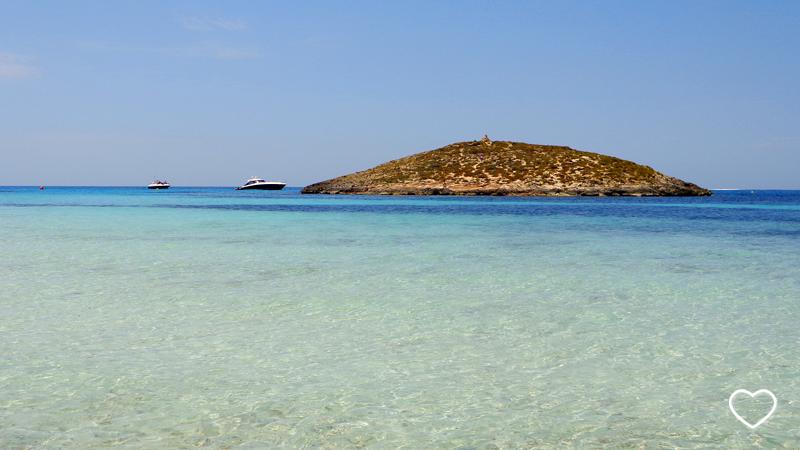 Uma ilha ao horizonte. O mar é transparente perto da costa e azul de diferentes tons mais ao longe.