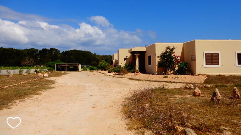 Estrada de terra e casas de arquitetura bem simples: praticamente cubos de cor bege.
