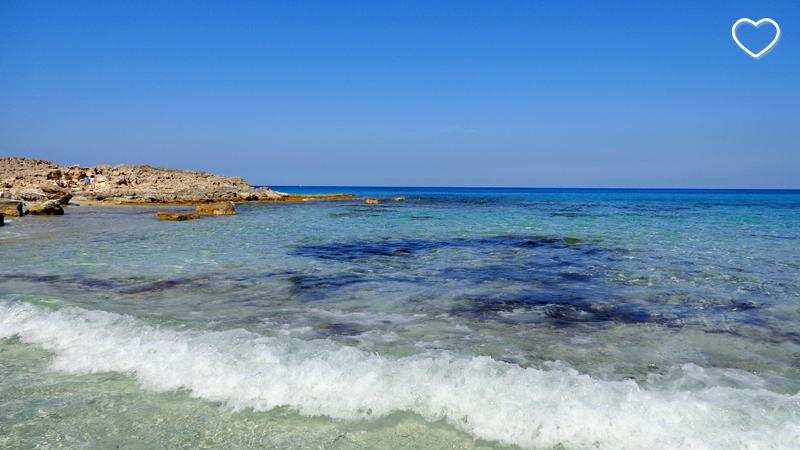 Praia de águas cristalinas e de diferentes tons de azul.