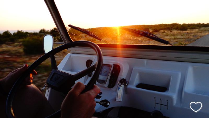 Detalhe de um volante e as mãos de uma pessoa dirigindo um carro sob o sol poente.