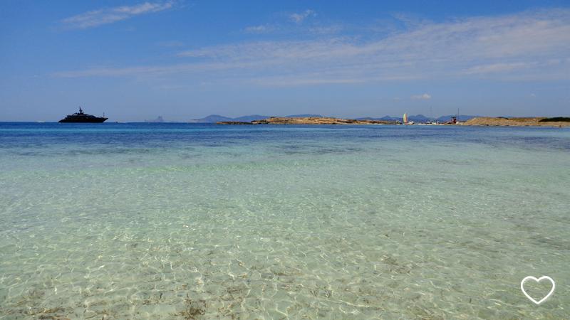 Um iate no horizonte. O mar de águas cristalinas e diferentes tons de azul sempre presente.
