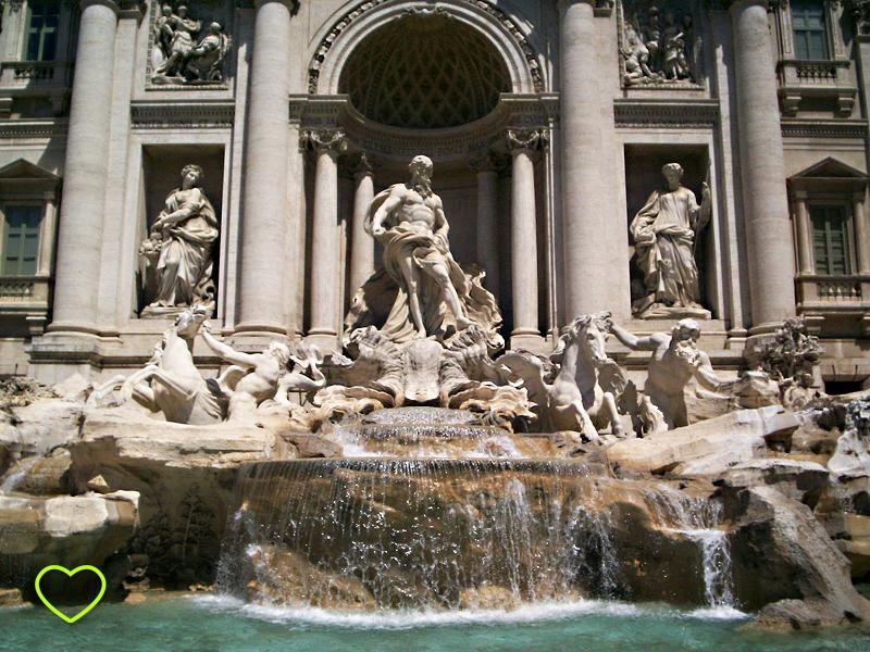 A Fontana di Trevi vista de frente. Aparece um pouco da água, verde. Mas o destaque é para as esculturas da fonte.