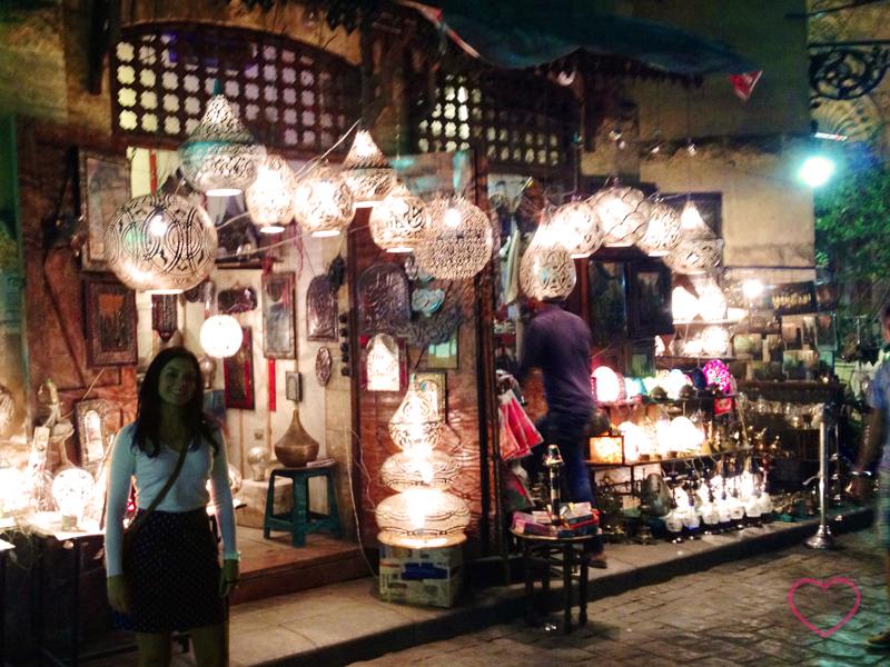 Eu em uma rua no centro histórico do Cairo, à noite. Estou diante de uma loja de luminárias, que estão acesas.