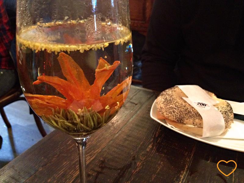 Foto de uma taça transparente com a flor de chá desabrochada dentro. Ao fundo, um sanduíche tipo bagel.