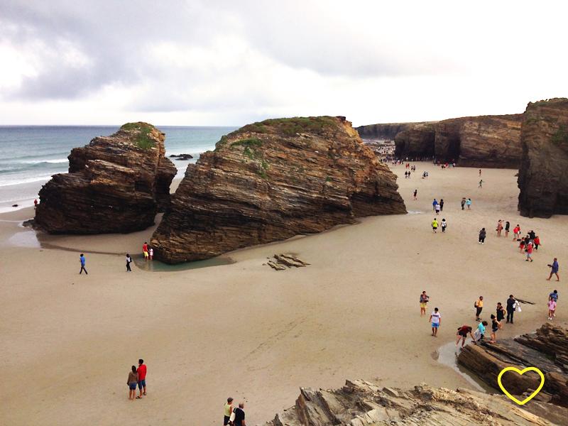 """Imagem da praia, vista do alto de uma pedra. Vêem-se seis rochas de uns 15 m de altura em média. São rochas com várias camadas e """"esculpidas"""" pela erosão. Pela areia, pessoas em fila passeiam."""