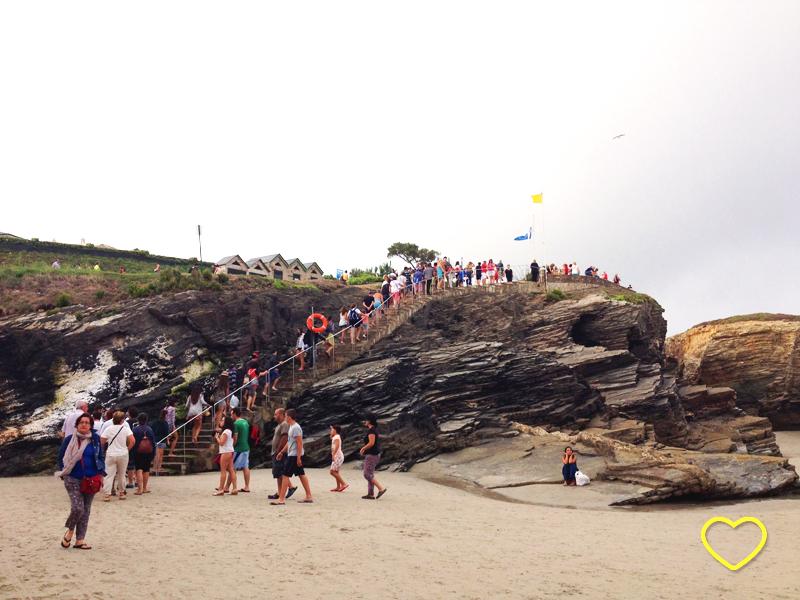 Pessoas em fila descem por um caminho em uma rocha para acessar a areia da praia.