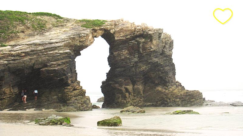 Rocha em forma de arco, na praia.