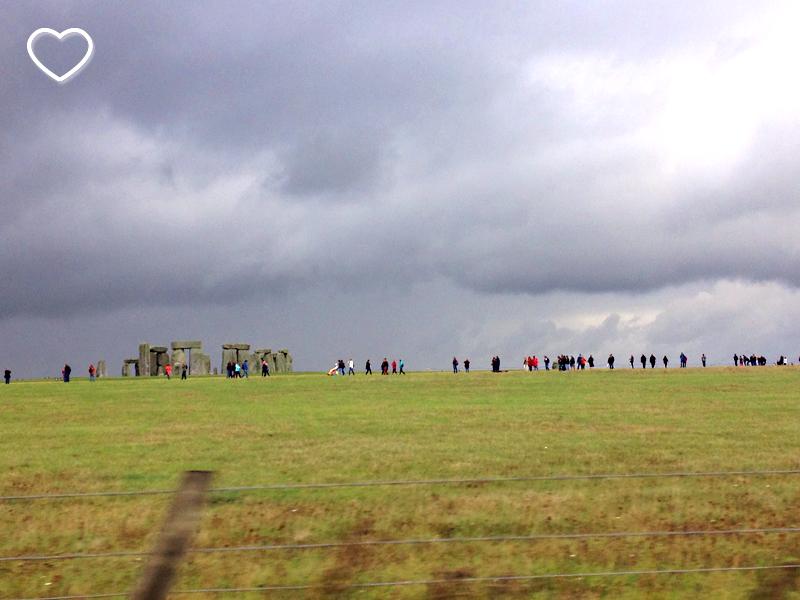 Foto de Stonehenge ao longe, rodeada de visitantes. Vê-se um gramado ver de um céu com nuvens escuras.