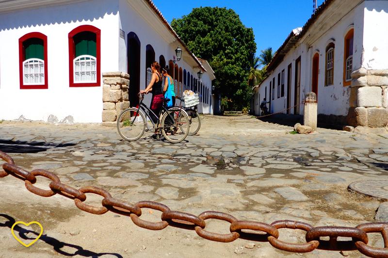 Foto de uma das ruas do Centro Histórico, com a pavimentação de pedras de tamanhos irregulares. Em primeiro plano se vê uma corrente que impede a passagem e automóveis.