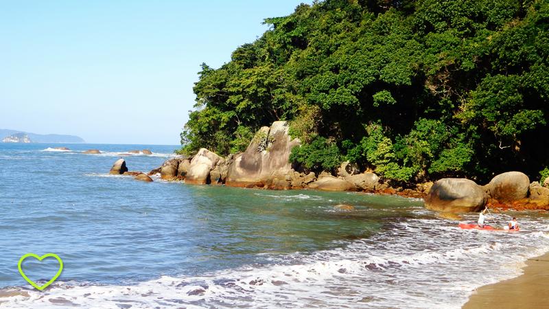O mar azul em um dia de sol. A espuma que chega do mar à areia é branca e limpa. Uma parte de um monte está como que lançado ao mar e revestido de uma vibrante e verde vegetação.