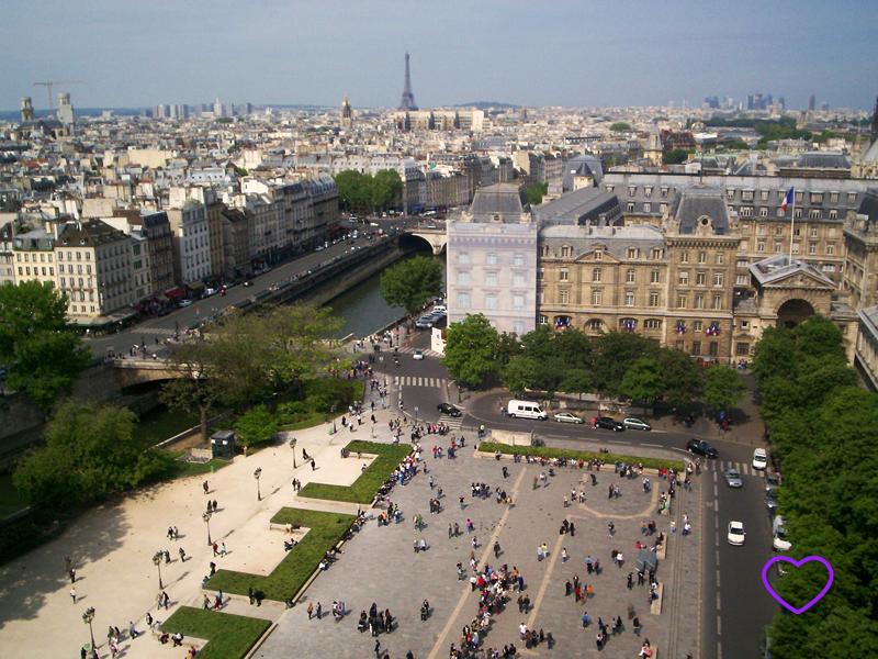 Foto de Paris do alto da Catedral de Notre Dame. Vê-se um pátio com muitas pessoas, o rio, muito edifícios e, ao fundo, a Torre Eiffel.