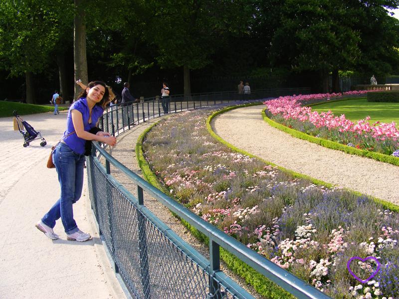 Eu ao lado de um jardim com flores.