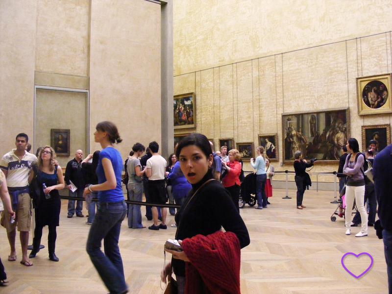 Foto minha no Louvre. Vê-se a Monalisa ao fundo.