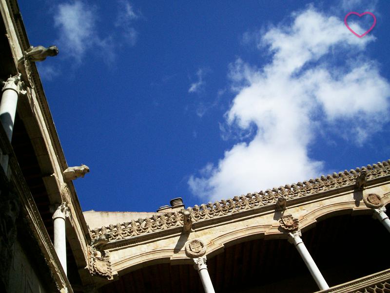 Céu azul e um enquadramento de baixo para cima do ângulo reto entre duas paredes de um pátio interno. Vê-se uma nuvem que eu acho que tem forma de burro.