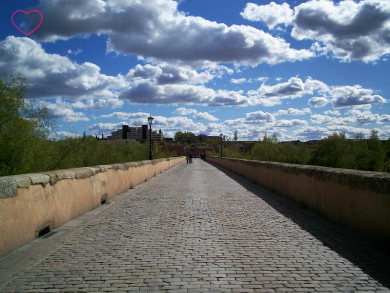 A ponte vazia e um céu azul com nuvens bem cheias e brancas.