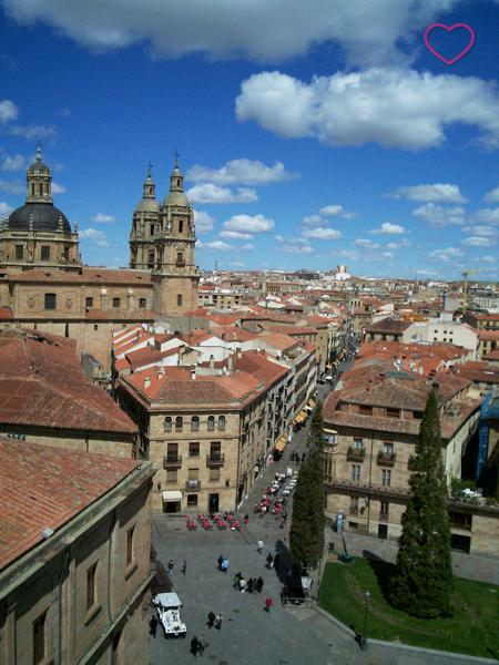 Vista do alto da cidade. Muitos edifícios históricos e com telhado e cor alaranjada. O céu azul mas com nuvens espaçadas.