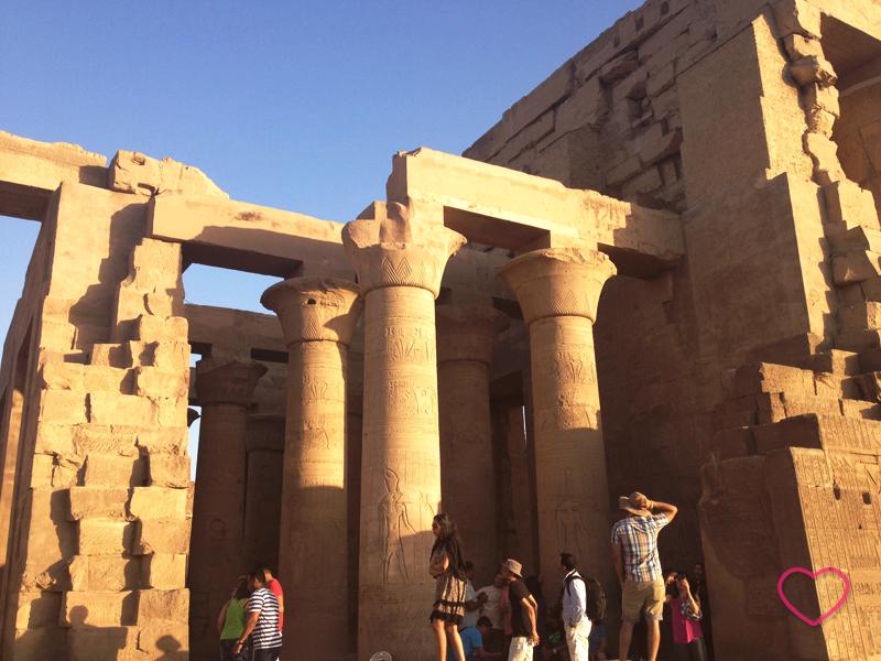 Ruínas do Templo de Kom Ombo e alguns turistas em um final de tarde ensolarado.