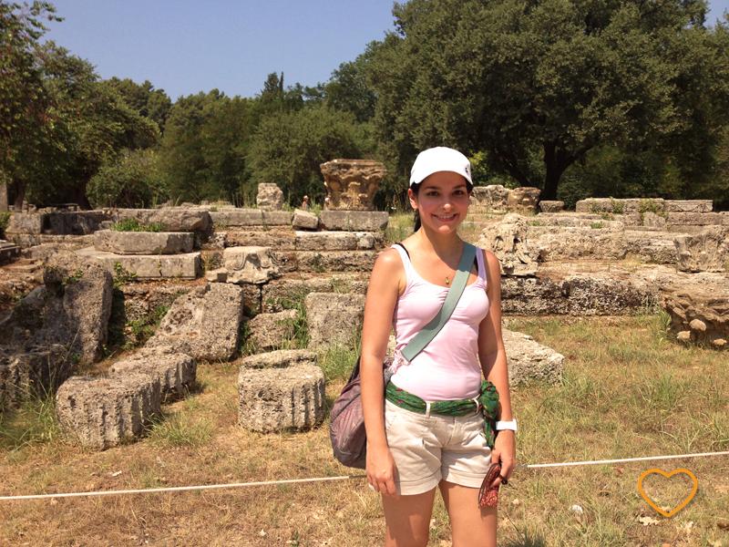 Eu no sítio arqueológico de Olímpia. Vêem-se ruínas atrás.