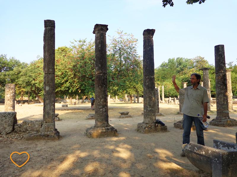 O guia explicando sobre Olímpia. Vêem-se colunas das ruínas.