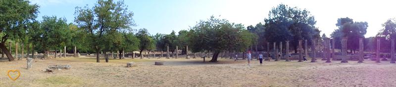 Panorâmica de uma parte do sítio arqueológico. Árvores e uma concentração de colunas.