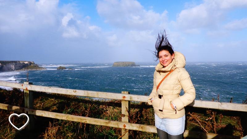 Eu, de cabelo em pé pelo vento. Ao fundo se vê o mar.