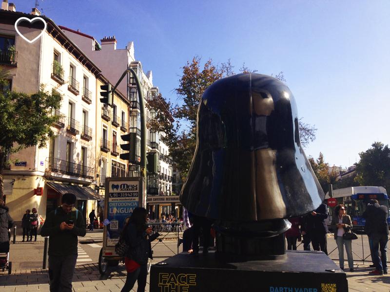 O capacete de Darth Vader, de costas. Ao fundo, edifícios.