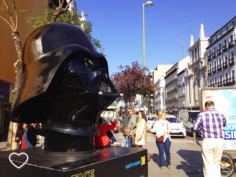O capacete do Darth Vader de frente. Ao fundo, edifícios.