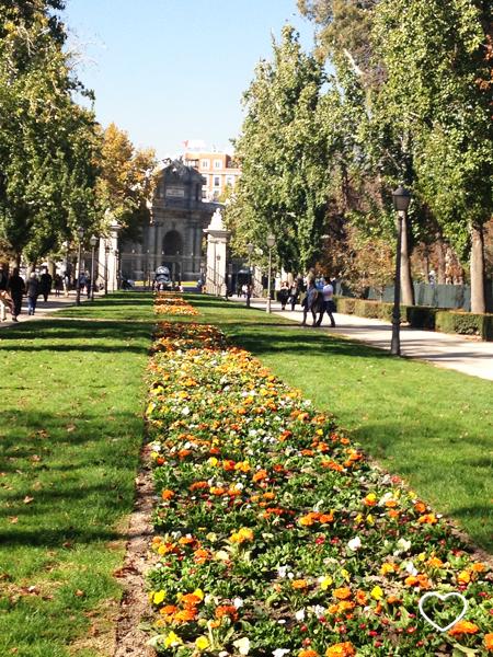 """Foto feita de dentro do Parque del Retiro. Um """"tapete"""" de flores e, no ponto de fuga da fotografia, a Puerta de Alcalá e o capacete de First Order Stormtrooper."""