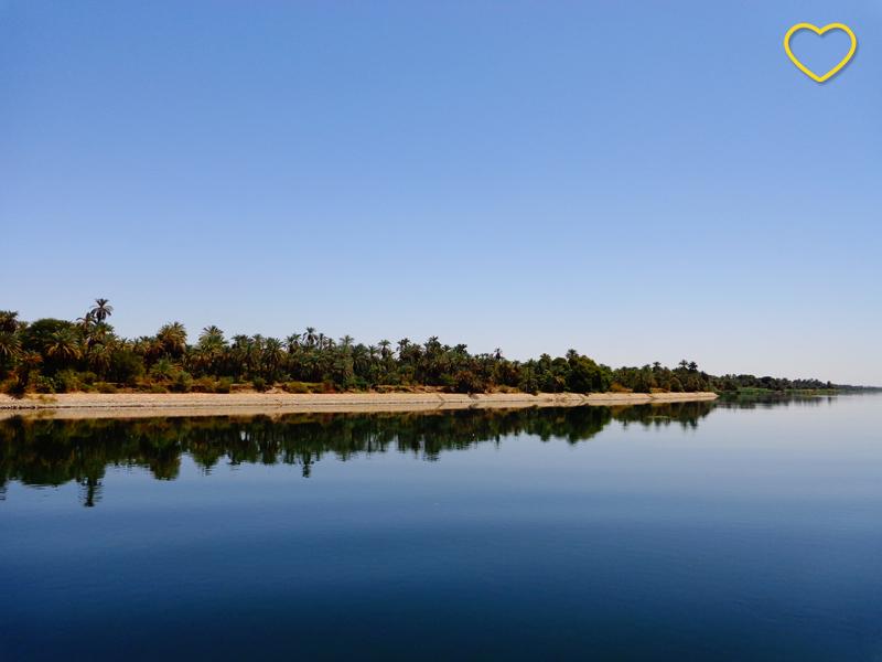 O rio e o céu azuis. E, na linha do horizonte, uma estreita faixa de areia e uma de vegetação. A areia e a vegetação são refletidas na água do rio.