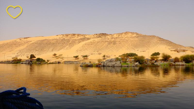 Pequenos morros desérticos de tom amarelado e refletidos nas águas do rio.