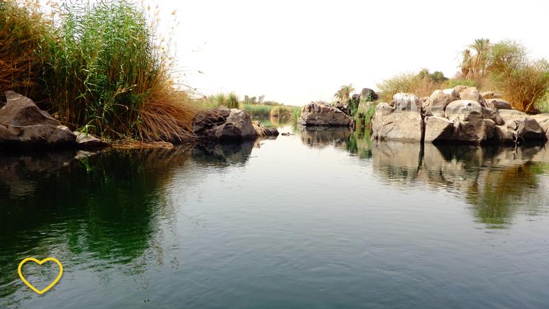 Uma reentrância do rio e muitas rochas. Vê-se alguma vegetação.