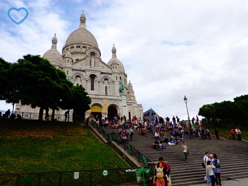 A basílica de Sacre Coeur e parte de sua escadaria, cheia de gente.