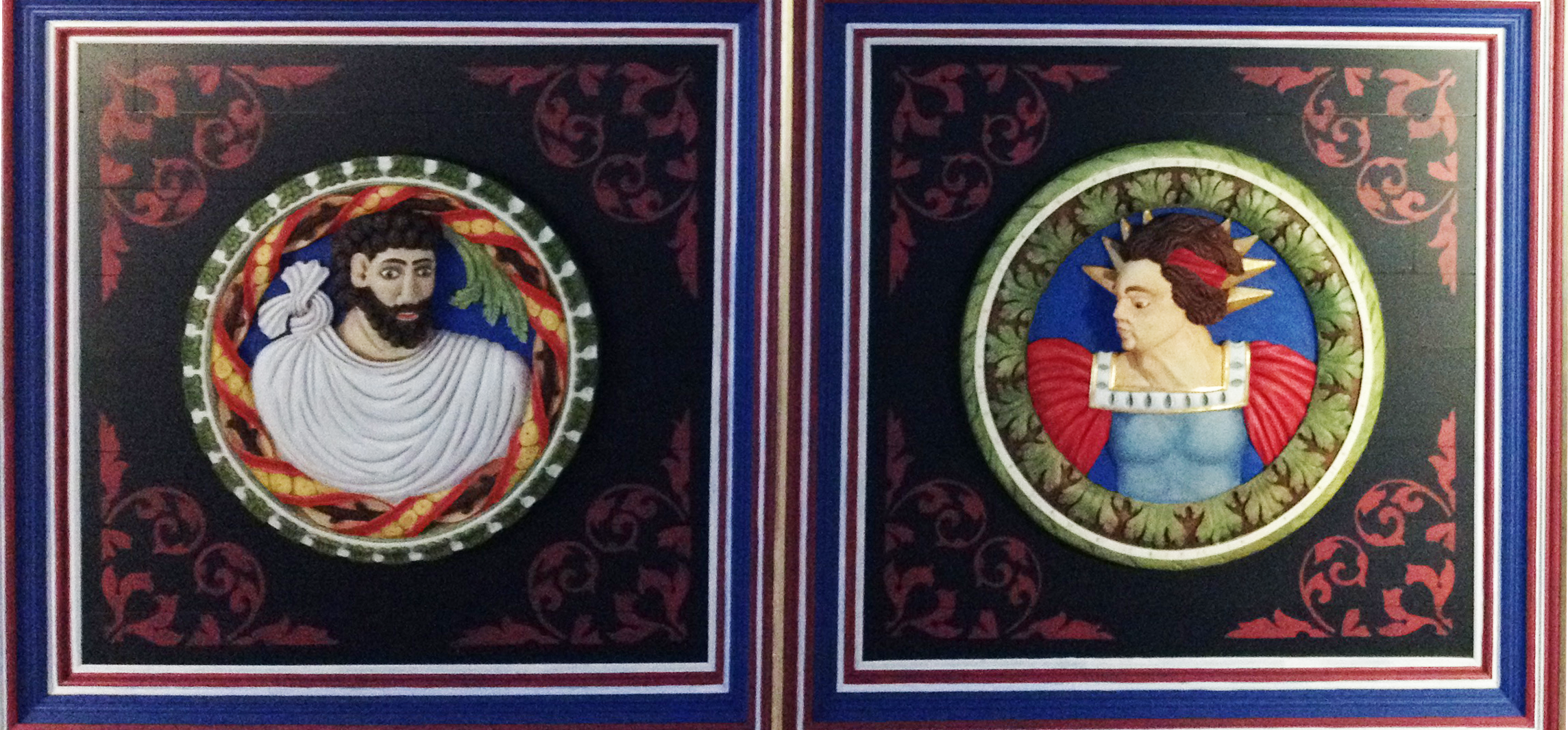 """Duas das """"cabeças"""" esculpidas em madeira no teto. São bem coloridas."""