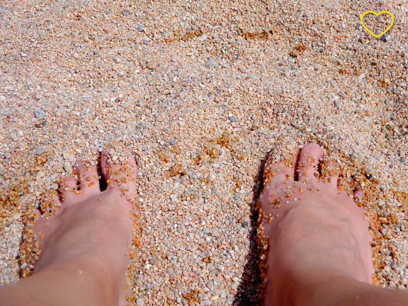 Meus dois pés em cima da areia da praia. A areia é grossa e a cor dos grãos varia entre beges e cinzas escuros.