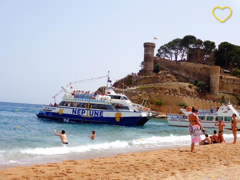 Na praia se vê a areia, o mar bem azul e um barco chegando com turistas. Também se vêem pessoas na água e a muralha ao fundo.