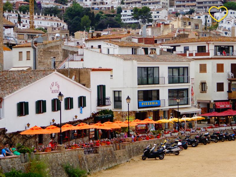 A orla da praia vista da praia. Muitos bares, casas, prédios baixos e mesas com guarda-sóis. E motos estacionadas.